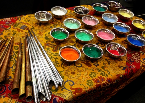 silver cups of colored sand, silver and copper horns nearby, used to gently sift colors onto the curlicues and filagrees of the mandala's expanding circle.